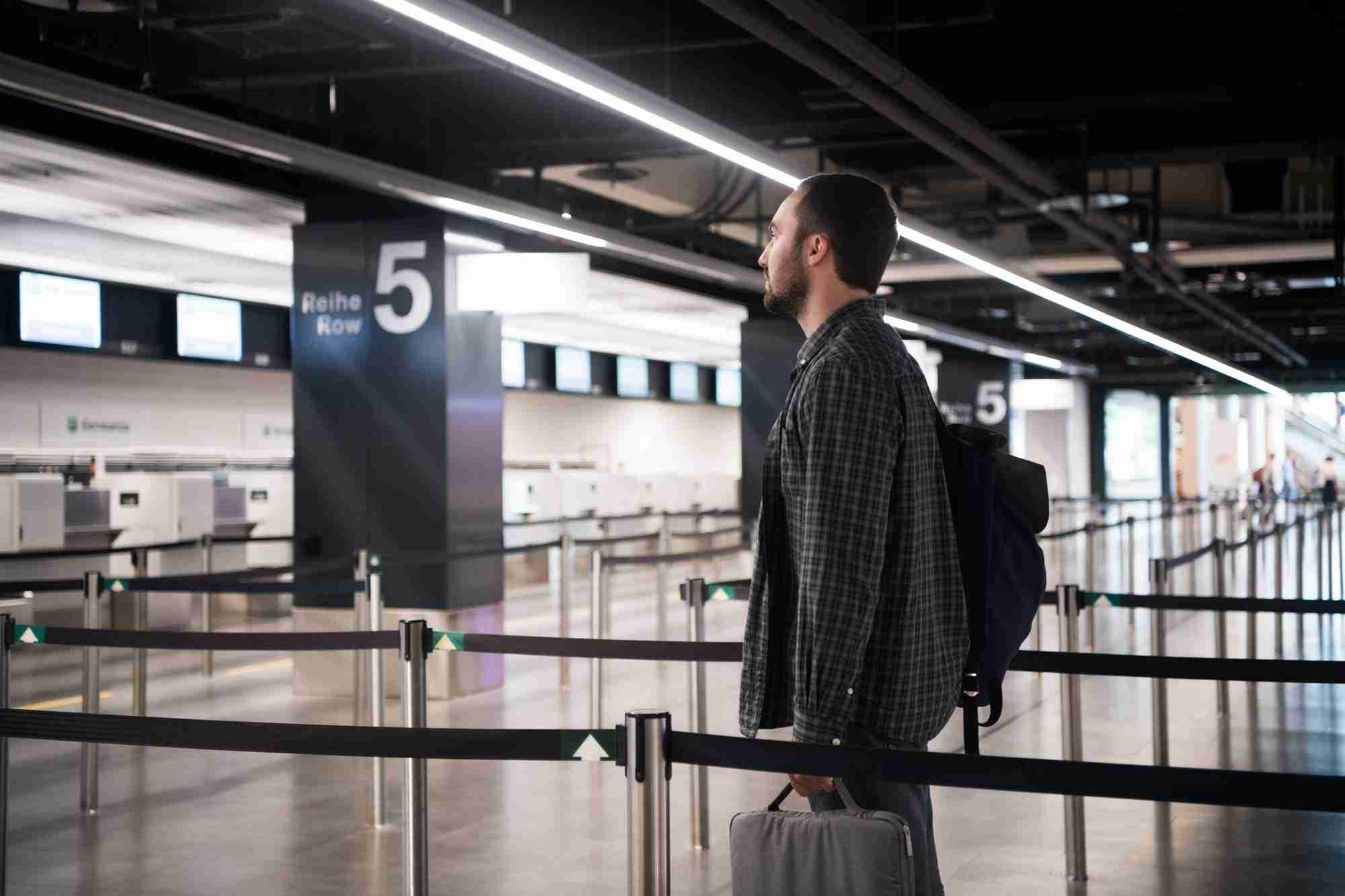 Young man with his luggage and backpack using smartphone while waiting for airline flight in the
